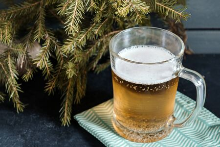 1 mug of light barley beer on a napkin on the background of fir branches