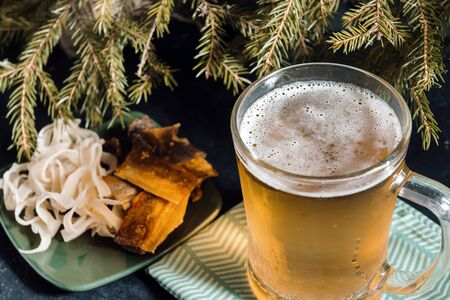 1 mug of light beer with squid rings and pieces of fish on the background of fir branches Фото со стока