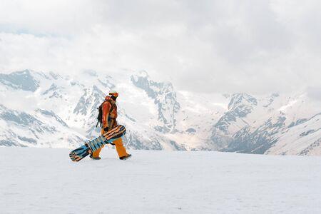 homme, snowboarder avec un snowboard à la main est sur la neige dans les montagnes, Caucase, athlète
