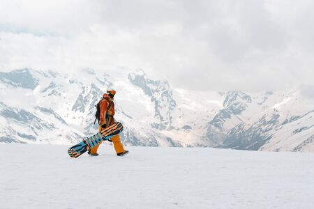 man, snowboarder with a snowboard in hand is on the snow in the mountains, Caucasus, athlete Imagens