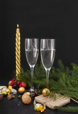 spruce branches, 2 glasses of champagne, chocolates with Golden wrappers, gift box, candle, balloons, sparkling wine, Christmas decor Stock fotó