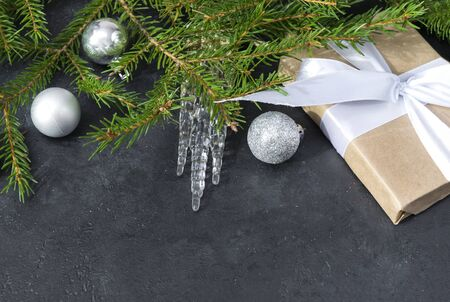 fir branches, glass icicle,  silver balls, gift box with white ribbon on black background, Christmas Stock fotó