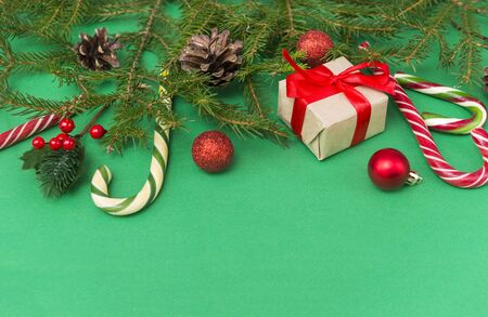fir branches on a green background, red balls,  gift box with a red ribbon, cones, cinnamon sticks, lollipops, a slice of dried orange,