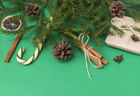 fir branches on a green background, a gift box, cones, cinnamon sticks, Lollipop,  slice of dried orange 版權商用圖片