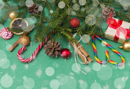 fir branches on a green background, a gift box with a red ribbon, cones, Golden and red balls, cinnamon sticks,  Lollipop, top view