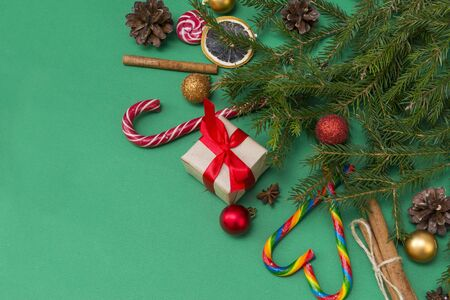 fir branches on a green background, a gift box with a red ribbon, cones, Golden and red balls, cinnamon sticks, candy, top view