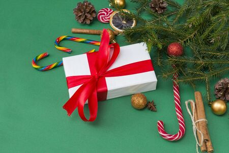 fir branches on a green background, a gift box with a red ribbon, cones, Golden and red balls, lollipops, cinnamon sticks, 版權商用圖片