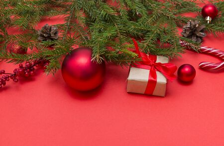 fresh spruce branch on a red background, red balls, candy, gift box with a red ribbon, candy, cones, branch with red berries, Christmas still life