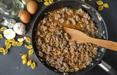 meat gravy to pasta in a frying pan with a wooden kitchen spatula, cooking, eggs, spices,