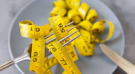 yellow measuring tape on a fork over a gray plate on a gray background closeup, diet,