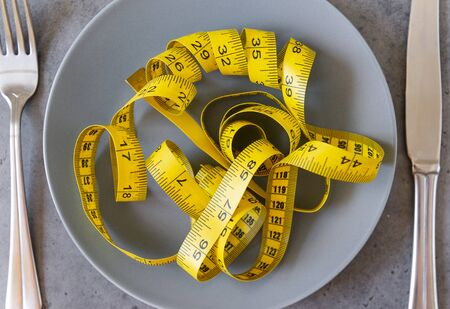 yellow twisted measuring tape on a brown plate on a gray background