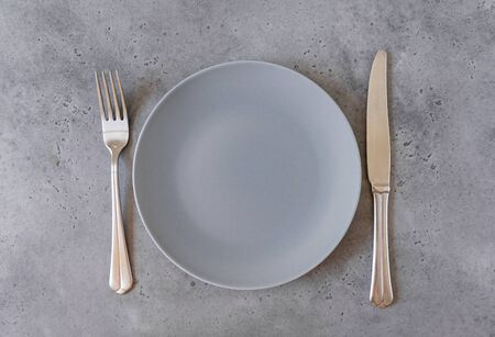 1 empty grey round plate, fork, knife on grey concrete background, top view