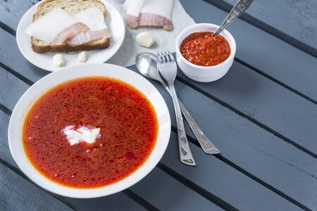 plate of borscht with sour cream, a piece of bacon on bread, garlic, ketchup, top view, red Ukrainian soup