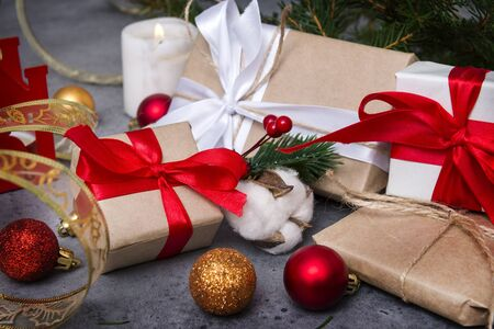 gift boxes with white and red ribbons, candle, fir branches, cotton twig, red and Golden balls, Christmas, new year Banco de Imagens