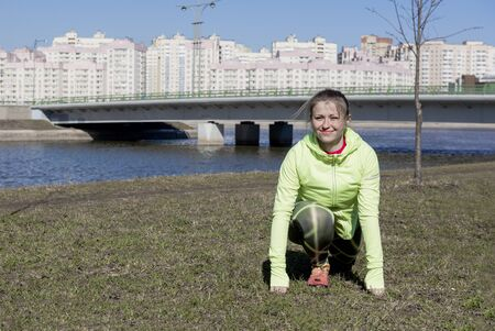 1 white young woman in sportswear xercise,  on the street in the city on the river Bank against the background of buildings and bridge