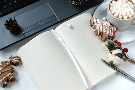open notebook with blank sheets, a laptop, a Cup of hot chocolate with marshmallows, a Christmas tree-shaped cookie, a cherry, a pen ,a sprig of cotton and red berries, copy space Reklamní fotografie