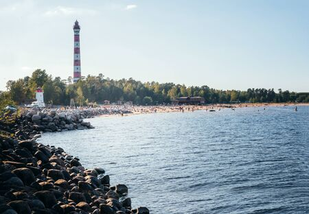 old lighthouse on the rocky shore  with a beach on Ladoga, people on the beach on a Sunny day