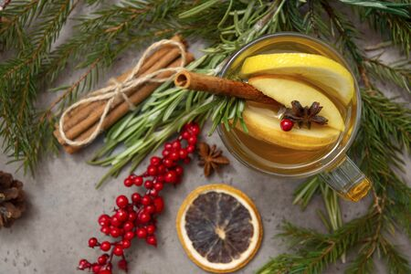1 Cup fruit tea with Apple and lemon,  fir branches,  cinnamon, star anise, rosemary, Lollipop, red berries cone on a gray background, top view,  Stock Photo