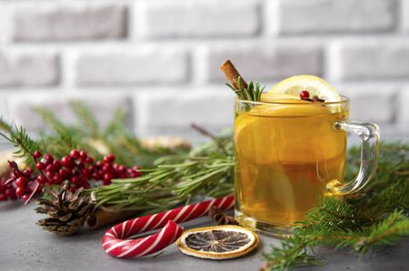 1 Cup fruit tea with Apple and lemon, cinnamon, spruce branches, rosemary, Lollipop, red berries on a gray background, Stock Photo