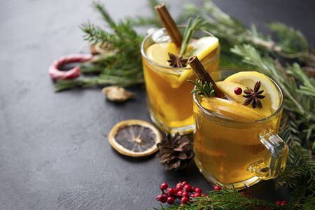 2 cups of hot tea with slices of Apple and lemon, cinnamon, star anise, rosemary sprigs on a background of fir branches on a black background