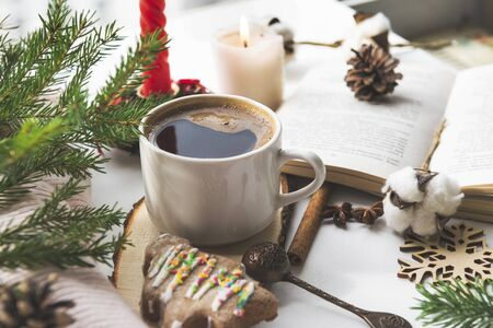 Cup of hot black coffee near the window, a Christmas tree shaped cookie, fir branch, an open book, cones, cotton branch,  candle