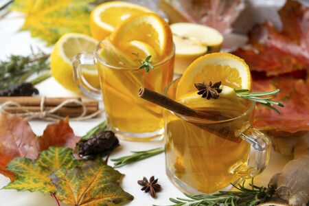 2 cups of fruit tea with orange and lemon, rosemary, cinnamon stick, ginger, star anise on a background of maple leaves