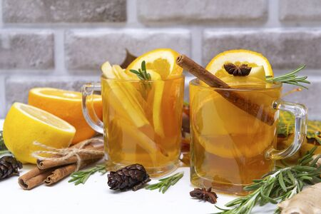 1 Cup of fruit tea with orange and lemon, cinnamon stick, rosemary, ginger, star anise  on a brick wall background,