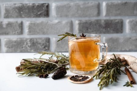 1 Cup of tea with rosemary, star anise, on a gray background, cone, slice of dried orange, ginger