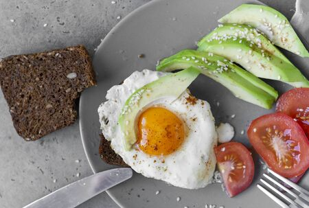 sandwich with eggs and avocado and tomato on a plate, sesame, piece of bread, knife, fork on gray background, Breakfast