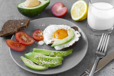 sandwich with eggs and avocado and tomato on a plate, sesame, a piece of bread, a glass of milk on a gray background, fork, knife, Breakfast Stock fotó