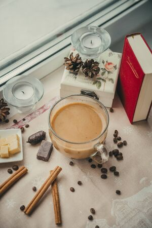 1 Cup of coffee with milk near the window, book, cinnamon sticks, pieces of cheese, candy, cones, candles Imagens