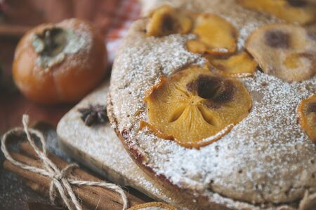 homemade cake with persimmon slices and powdered sugar and cinnamon close up, dissert,