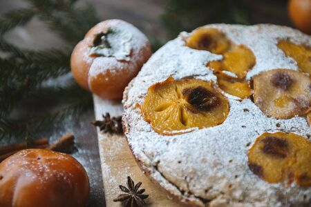 homemade cake with pieces of persimmon and powdered sugar, star anise, spruce branches, top view, Stock fotó