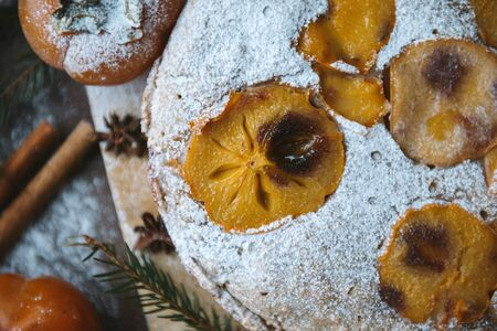 homemade cake with slices of persimmon and powdered sugar, view sverhu, flat lay