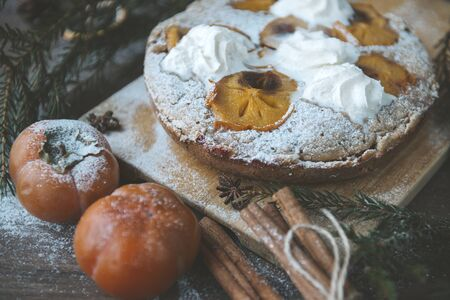 homemade cake with persimmon and whipped, fresh persimmon, cinnamon, spruce branches, star anise