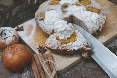 pie with persimmon on the cutting Board, fresh persimmon, knife, cinnamon, spruce branches, star anise