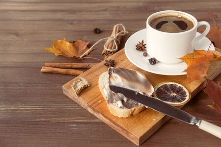 piece of wheat bread with chocolate cream, a 1 Cup of black coffee ,  autumn maple leaves, cinnamon, star anise, piece of dried orange, knife; wooden background,  Stock fotó