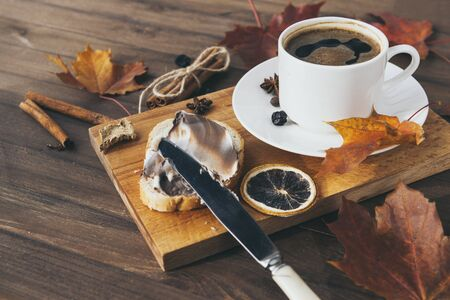 piece of wheat bread with chocolate cream, a Cup of black coffee on the Board, autumn maple leaves, cinnamon, star anise, a piece of dried orange, knife; wooden background