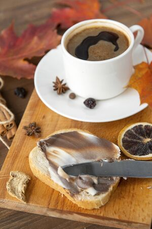 piece of wheat bread with chocolate cream, a Cup of black coffee on the Board, autumn maple leaves, cinnamon, star anise, a piece of dried orange