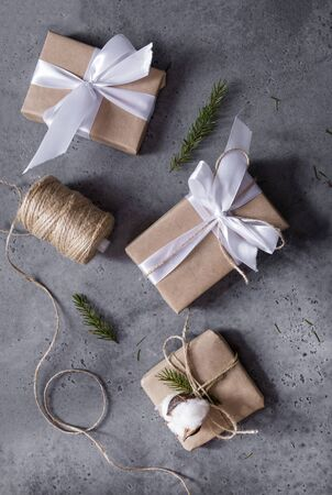 2 gift boxes wrapped in Kraft paper, with white ribbon and rope, silver balls, reel with rope, spruce branches on a gray background, top view