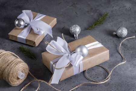 2 gift boxes wrapped in Kraft paper, with white ribbon and rope, silver balls, reel with rope, spruce branches on a gray background