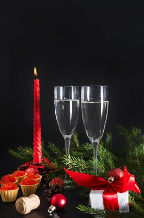 2 glasses of champagne, red candle, tartlets with red caviar, gift box with red ribbon , fir branches  on a black background Stockfoto