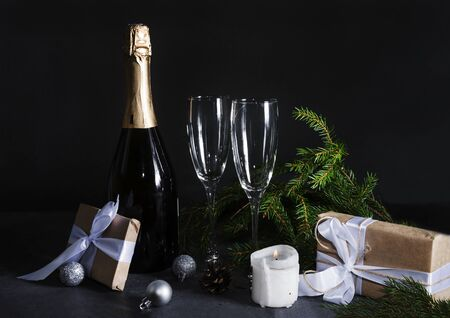 1 bottle of champagne, 2 glasses, fir branches in the dark on a black background, gift box with white ribbon, silver balls, candle, copy space Stockfoto