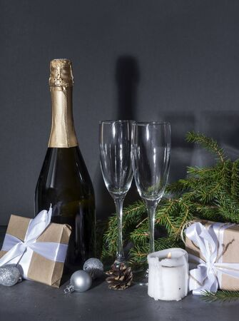 1 bottle of champagne, 2 glasses on the background of fir branches in the dark, gift box with a white ribbon, silver balls, candle, cone Stockfoto