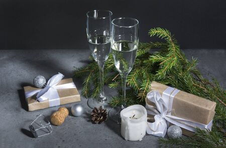 2 glasses of champagne on the background of fir branches in the dark, gift box with a white ribbon, silver balls, candle, cone Stockfoto