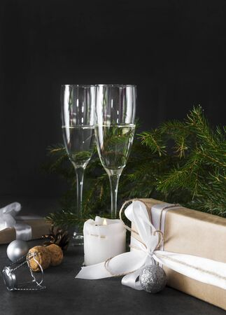 2 glasses of champagne on a background of fir branches in the dark, gift box with a white ribbon, silver balls, candle Stockfoto - 132099482