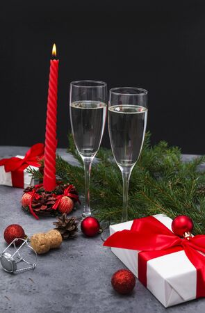 2 glasses of sparkling wine, champagne, red candle, gift box with red ribbon, balloons, spruce branch on a gray and black background, bottle stopper
