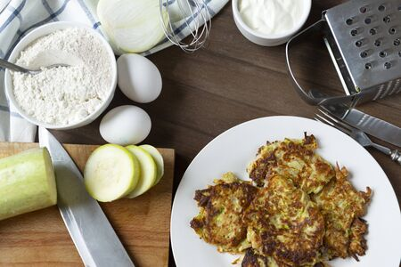 few zucchini pancakes on a white plate, sour cream on a brown wooden background, knife, eggs, pieces, fresh, raw, whisk, flour, onion, grater, 版權商用圖片