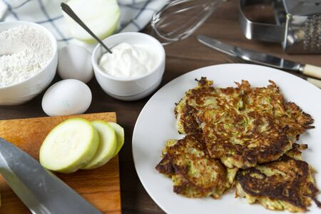 few zucchini fritters on a white plate, sour cream on a brown wooden background, a knife, eggs, pieces of fresh raw zucchini, a whisk, flour,