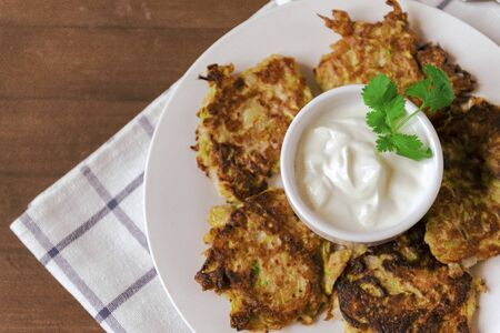 plate of zucchini fritters with sour cream and greens on poltice wooden background, top view,  copy space 版權商用圖片